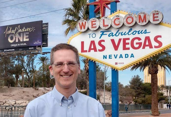 Drew Hannush living the 9-5 travel lifestyle in front of the Welcome to Las Vegas sign